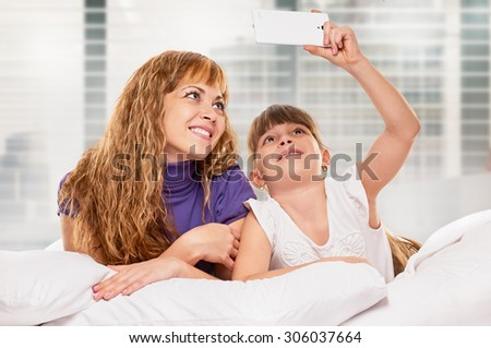 Mother and dauhter taking photo with her smart-phone camera in the bed on light window bakground - stock photo