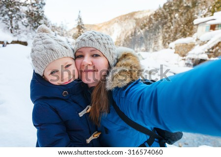 Mother and doughter taking selfie on beautiful winter day outdoors - stock photo