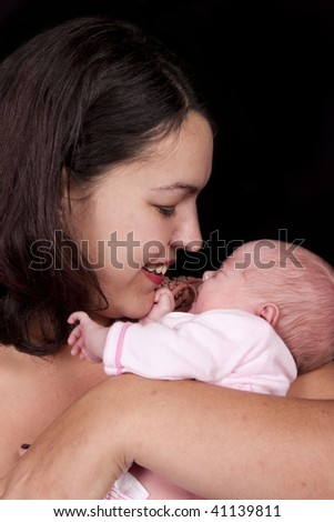 Mother and eight day old baby isolated on black