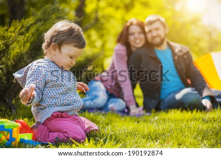 mother and father are playing with their daughter in the park - stock photo