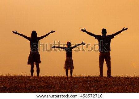 Mother and father enjoy watching sunset with their daughter. Family greeting the sunset