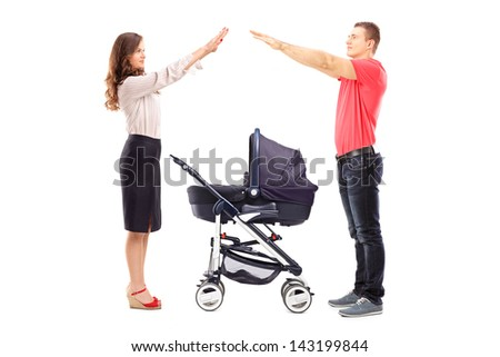 Mother and father gesturing with their hands protection above a baby carriage isolated on white background - stock photo