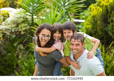 Mother and father giving children a piggyback - stock photo