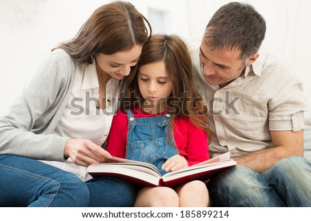 Mother And Father Helping Their Daughter While Reading Book - stock photo