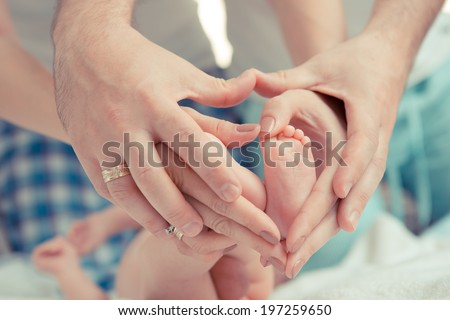 mother and father hold feet of newborn baby - stock photo