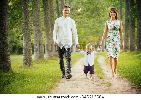 Mother and father holding hands with their little son walking on the forest road.