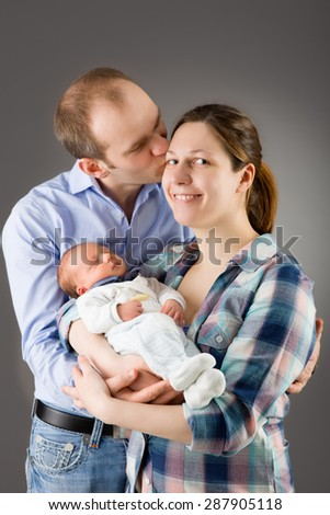 Mother and father holding their newborn baby - stock photo