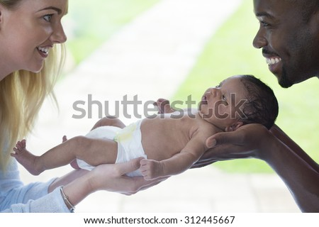Mother and Father holding their newborn baby. They are looking at each other and smiling.