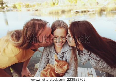 Mother and father kissing their preteen daughter outdoors. Photo toned style Instagram filters. - stock photo