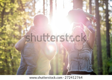 Mother and Father Lifting Children into the Air While Walking in Forest with Bright Sunlight Behind Them. - stock photo