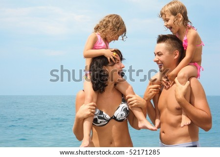 mother and father near water with two little girls sitting on their necks. woman looking at man and man looking at woman.