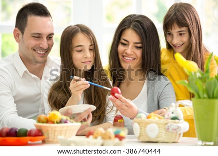 Mother and father painted eggs with their daughters - stock photo