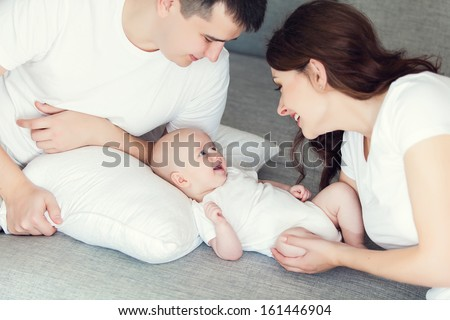 mother and father playing with their cute baby on the couch at home