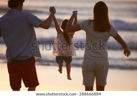 Mother and Father swinging Daughter up in the air at sunset at the beach - stock photo