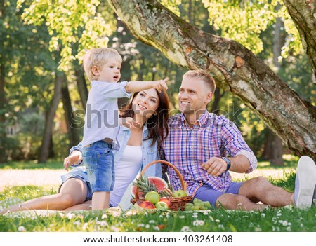 Mother and father with son enjoying their selves on the picnic eating fruits.
