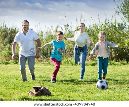 Mother and father with two kids playfully running after a ball outdoors - stock photo