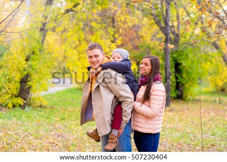 Mother and Father With Young Son On his back Autumn Park walks between trees, smiling together