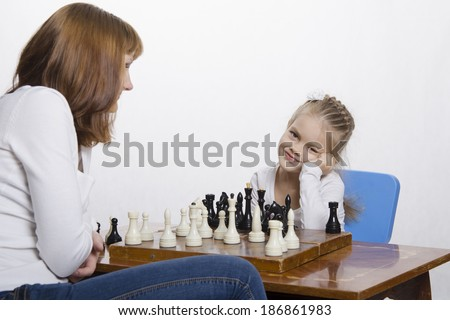 Mother and four-year-old daughter sitting at a table and play chess. Mom tells about the shapes