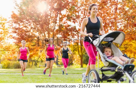 Mother and friends jogging - stock photo