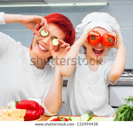Mother and funny daughter playing in the kitchen with vegetables - stock photo