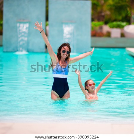 Mother and girl enjoying summer vacation in luxury swimming pool - stock photo