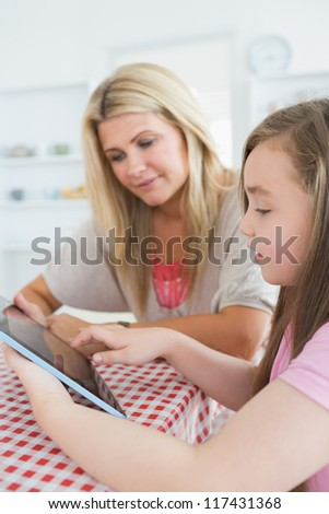 Mother and girl sitting while holding a tablet computer at the kitchen