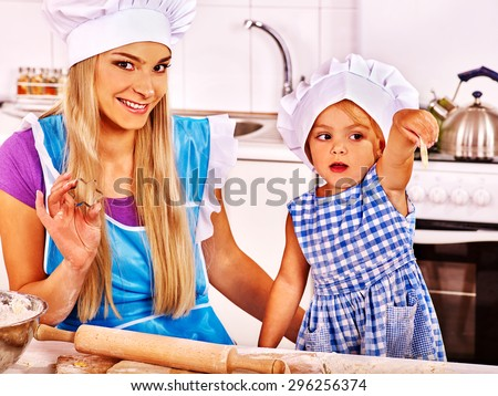 Mother and granddaughter baking cookies. Girl pointing. - stock photo