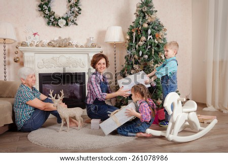mother and grandmother give children christmas gifts