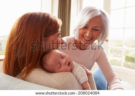 Mother And Grandmother With Sleeping Newborn Baby Daughter - stock photo