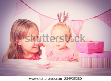 mother and happy little girl at first birthday party - stock photo