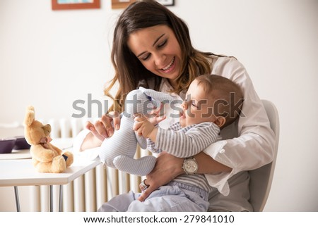 Mother and her baby boy playing with bunny toys.