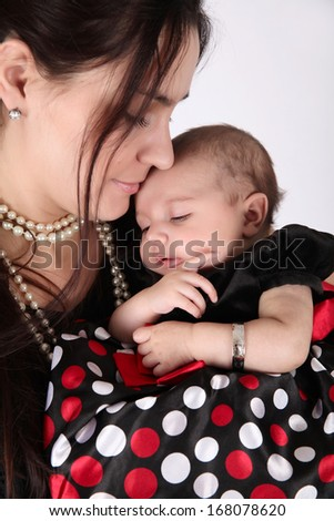 Mother and her baby daughter wearing black and red - stock photo