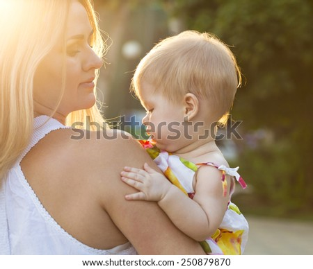 Mother and her baby enjoy the summer sunset - stock photo