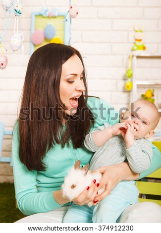 Mother and her baby girl holding little Easter rabbit - stock photo