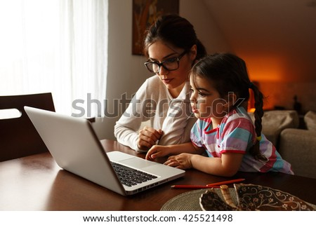 Mother and her baby girl watching cartoons on laptop.They sitting in living room.Natural light ambient.