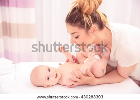 Mother and her baby on changing table in room