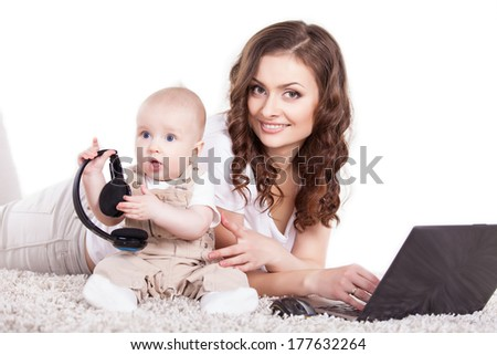 Mother and her baby playing around with a computer - stock photo