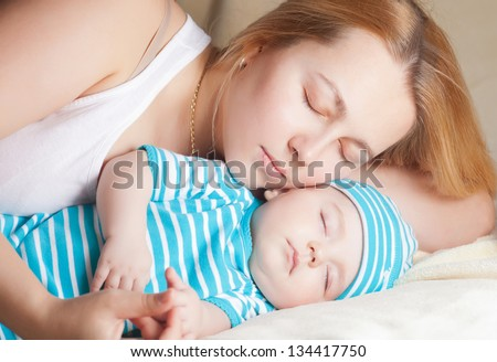 mother and her baby, sleeping in bed - stock photo