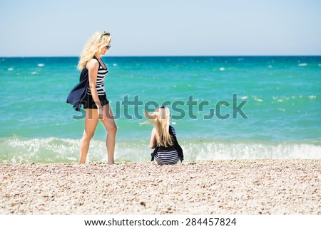 Mother and her charming daughter resting on the beach  - stock photo