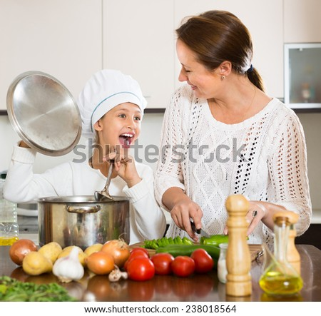 Mother and her cheerful daughter in cookers�¢??s hat preparing soup together. Focus on girl  - stock photo