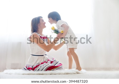 Mother and her child, embracing with tenderness and care, child  giving mother flowers. Mother day concept, happiness and love - stock photo