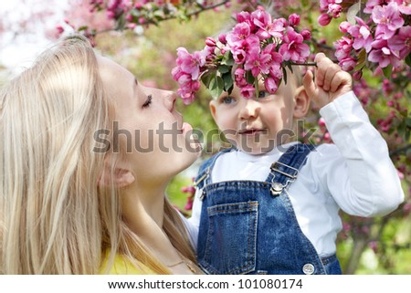 Mother and her child enjoy the early spring between flowers. - stock photo