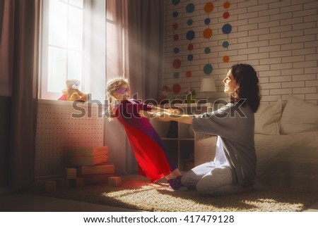 Mother and her child girl playing together. Girl in an Superman's costume. Happy loving family having fun. - stock photo