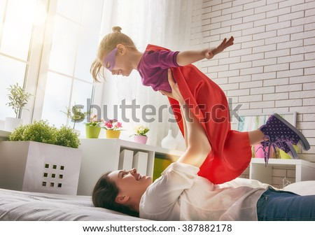 Mother and her child girl playing together. Girl in an Superman's costume. The child having fun and jumping on the bed. - stock photo