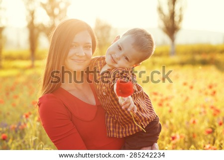 Mother and her child playing in spring poppy field in soft sunlight - stock photo
