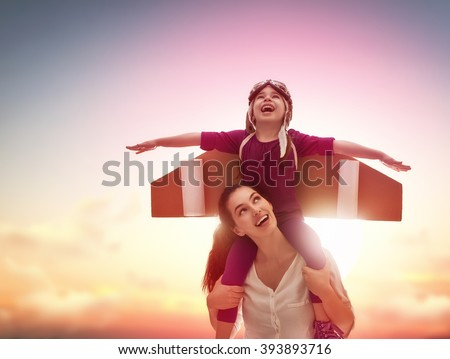 Mother and her child playing together. Little child girl plays astronaut. Child in an astronaut costume plays and dreams of becoming a spaceman. Happy loving family having fun.