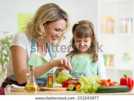 mother and her child preparing and tasting healthy food