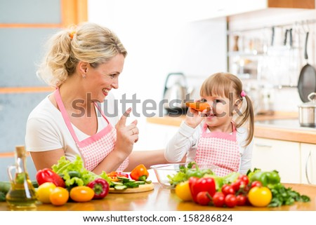 mother and her child preparing healthy food and having fun - stock photo
