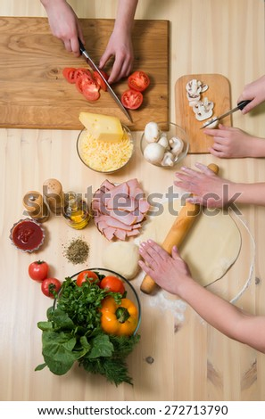 Mother and her children cooking pizza at home. Filling pizza with ingredients. Top view. Overhead view. - stock photo