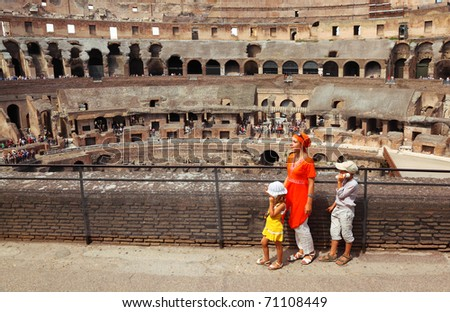 Mother and her children, daughter and son, with electronic guide standing in arena in Coliseum in Rome, Italy at sunny day - stock photo